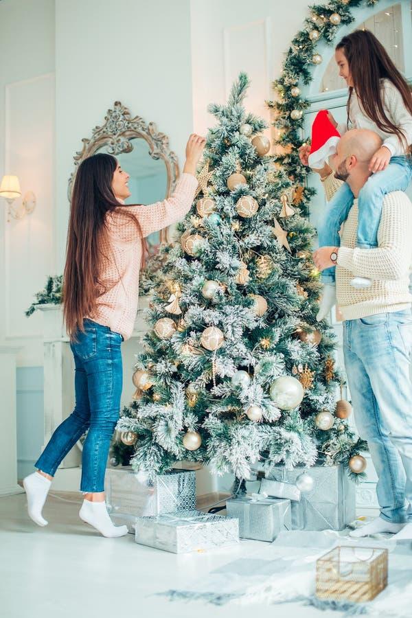 Ragazza sveglia e sua la madre che decorano abete sulla notte di Natale fotografia stock libera da diritti