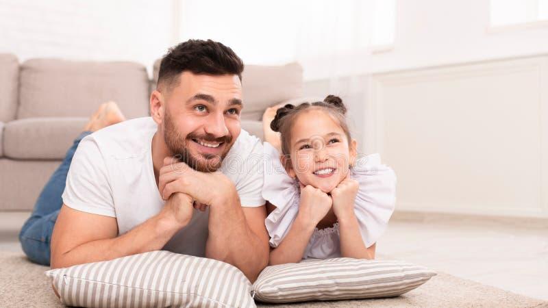 Ragazza sveglia e suo il sogno bello del papà, trovantesi sul pavimento fotografie stock
