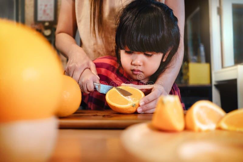 Ragazza sveglia felice di anni 3-4 con la sua fetta della mamma una certa arancia sulla Tabella di legno nella stanza della dispe fotografia stock