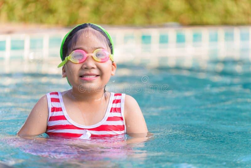 Ragazza sveglia nelle nuotate di un costume da bagno nello stagno immagine stock