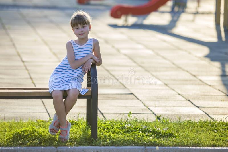 Ragazza sveglia sorridente che si siede da solo all'aperto sul banco il giorno di estate soleggiato fotografia stock libera da diritti