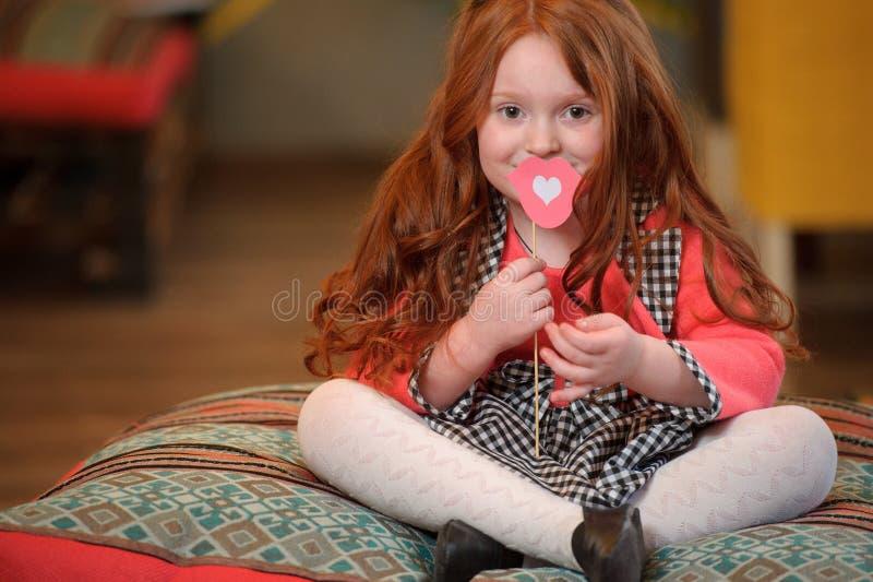 Ragazza sveglia sorridente del bambino che tiene giocattolo a forma di labbra con cuore fotografie stock libere da diritti
