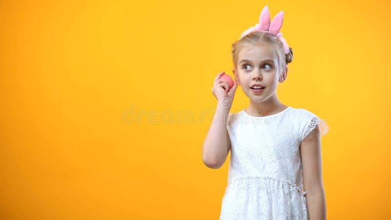 Ragazza sveglia in vestito bianco che ascolta per dentellare uovo su fondo giallo, festival immagini stock