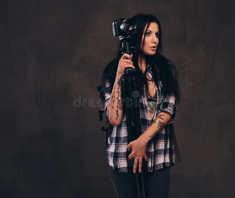 Ragazza tatuata seducente che indossa una ragazza controllata sbottonata della camicia che posa con una macchina fotografica fotografie stock