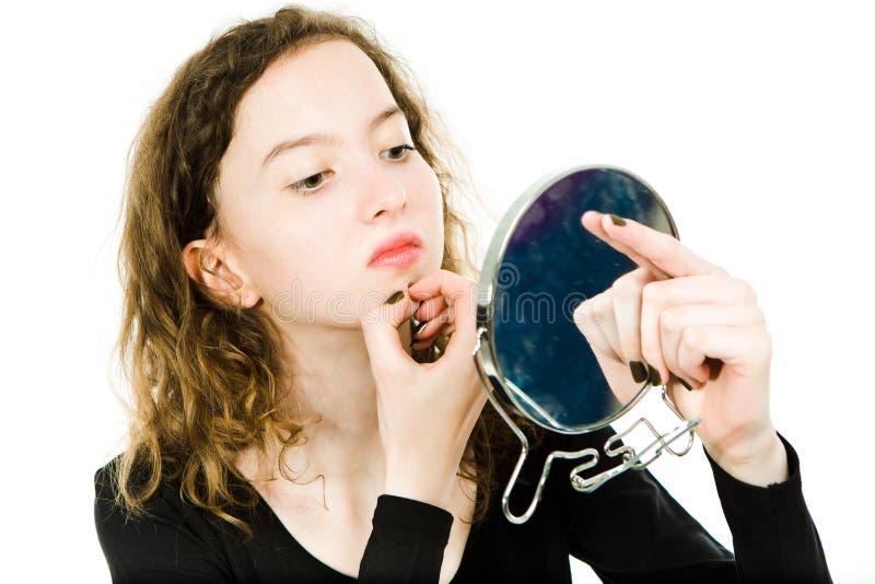 Ragazza Teenaged che controlla pelle in specchio - mento immagine stock libera da diritti