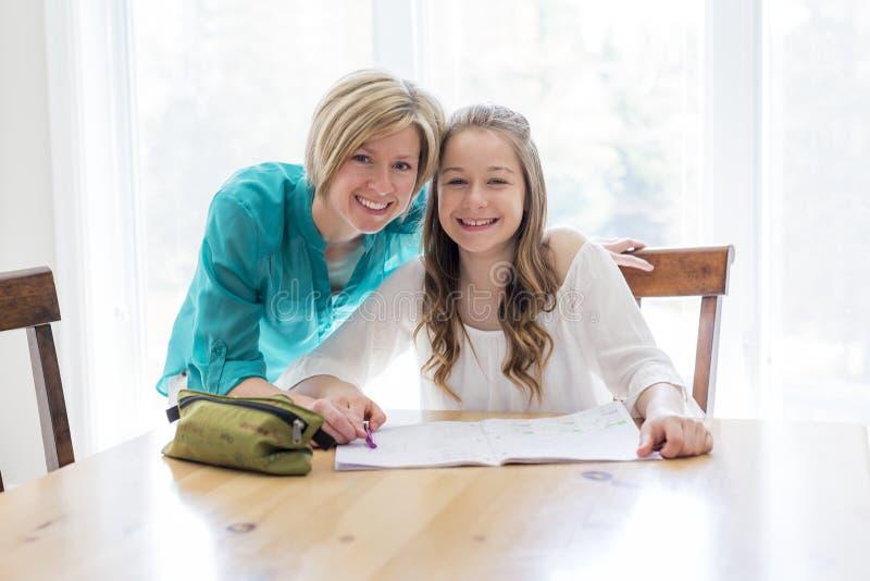 Ragazza teenaged d'aiuto della madre con compito immagini stock libere da diritti