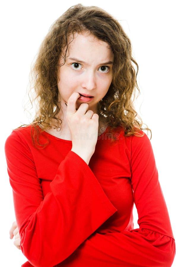 Ragazza Teenaged in vestito rosso che ha i dubbi e sforzo fotografia stock