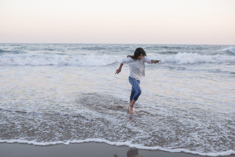 Ragazza teenager abbronzata che corre al tramonto sulla riva del Mediterraneo vestita in maglietta felpata e jeans bianchi fotografia stock