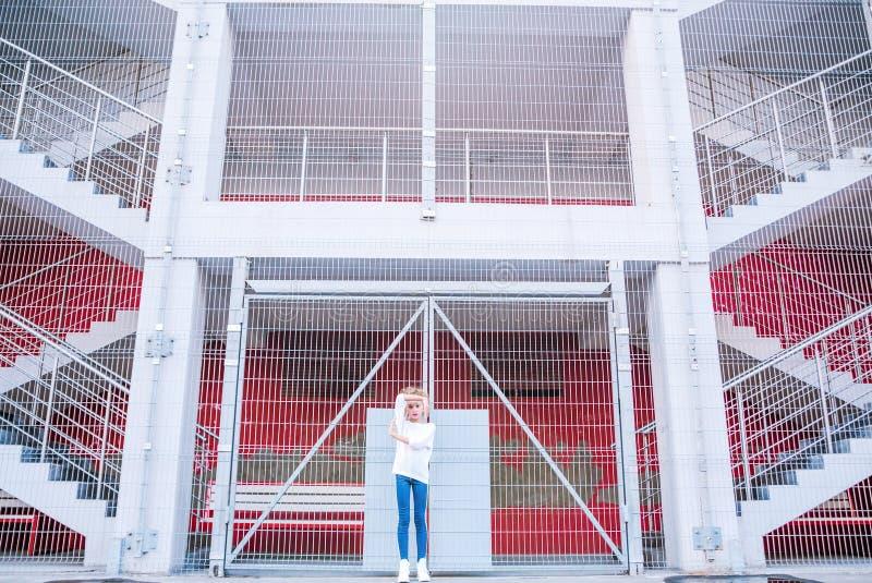 Ragazza teenager alla moda che posa contro un fondo di una costruzione e di una grata fotografia stock