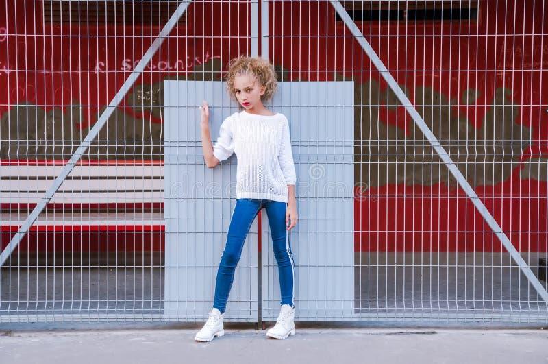Ragazza teenager alla moda che posa contro un fondo di una costruzione e di una grata immagini stock