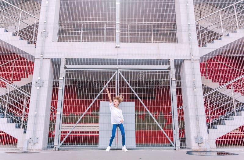 Ragazza teenager alla moda e felice che posa contro un fondo di una costruzione e di una grata immagine stock libera da diritti