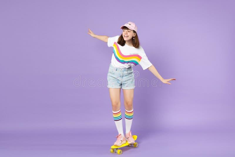 Ragazza teenager allegra in vestiti vivi che guidano le mani di diffusione del pattino giallo che guardano da parte isolate sulla fotografia stock libera da diritti