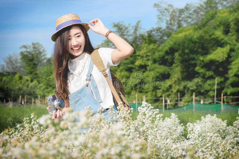 Ragazza teenager asiatica dei pantaloni a vita bassa graziosi in un giardino floreale bianco della molla, immagine stock libera da diritti