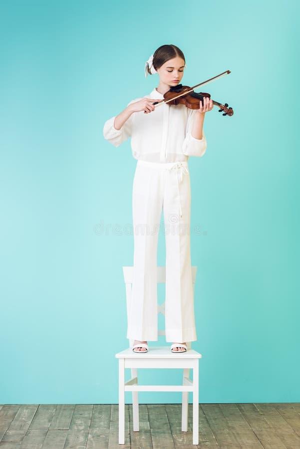 ragazza teenager in attrezzatura bianca che gioca violino e che sta sulla sedia fotografia stock libera da diritti