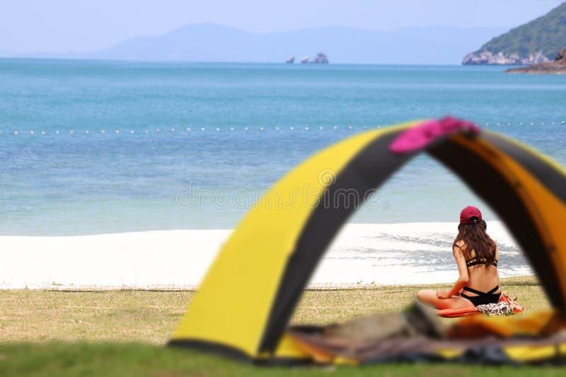 Ragazza teenager in bikini che si accampa e che si rilassa, tenda sulla spiaggia fotografia stock libera da diritti