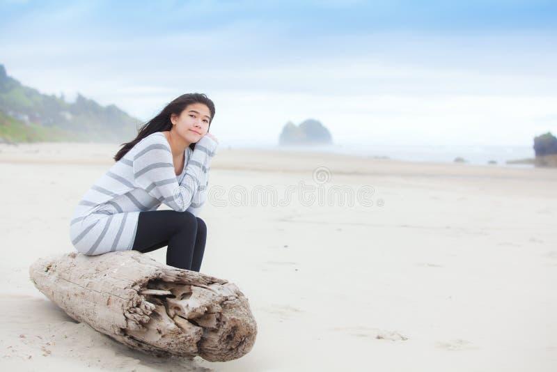 Ragazza teenager biraziale che si siede sul ceppo che esamina tranquillamente oceano fotografia stock libera da diritti