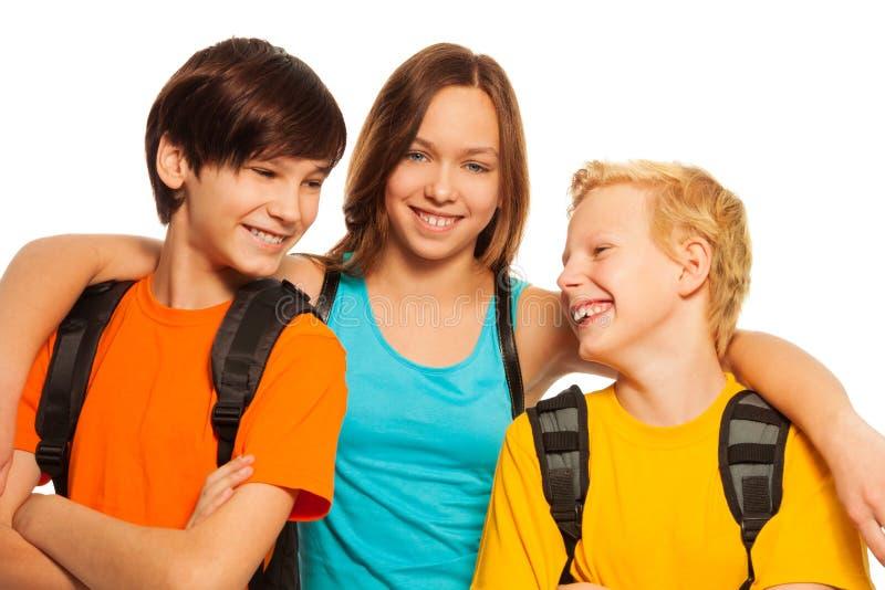 Ragazza teenager che abbraccia i suoi due amici fotografia stock