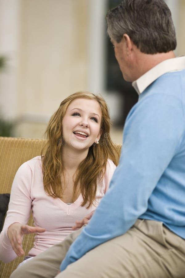 Ragazza teenager che conversa con il papà immagini stock libere da diritti
