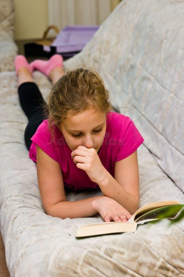 Ragazza teenager che legge un libro sul letto fotografia stock