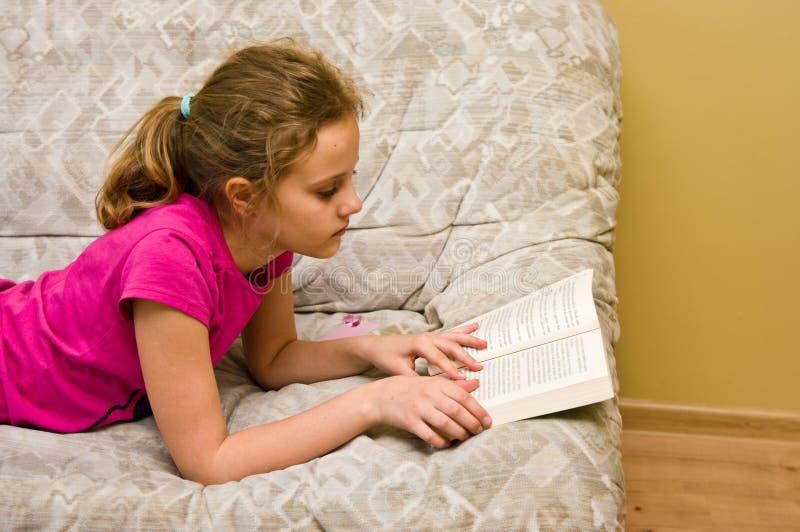 Ragazza teenager che legge un libro sul letto immagini stock