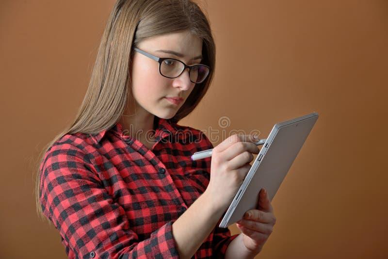 Ragazza teenager che per mezzo del computer della compressa fotografia stock libera da diritti