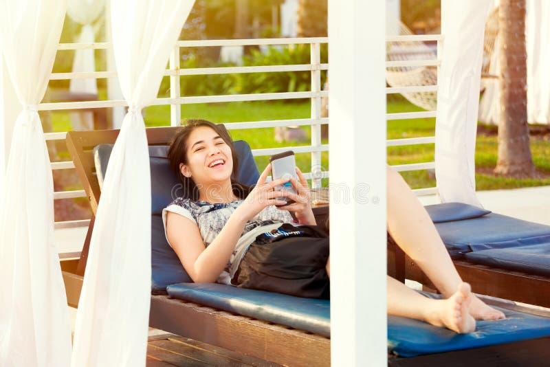 Ragazza teenager che per mezzo dello smartphone mentre rilassandosi sulla chaise-lounge alla località di soggiorno immagini stock