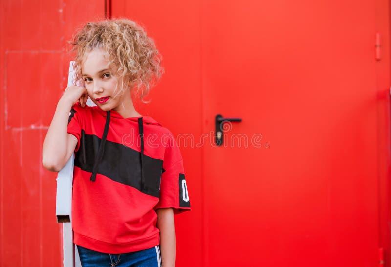 Ragazza teenager che posa sul fondo rosso della parete immagini stock