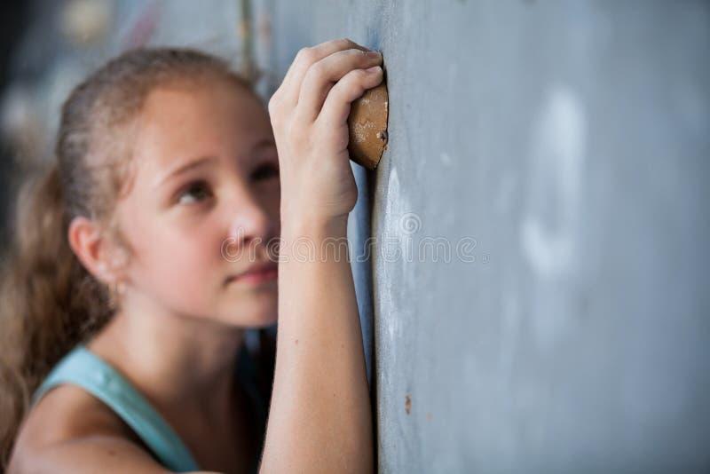 Ragazza teenager che scala una parete della roccia dell'interno fotografie stock libere da diritti