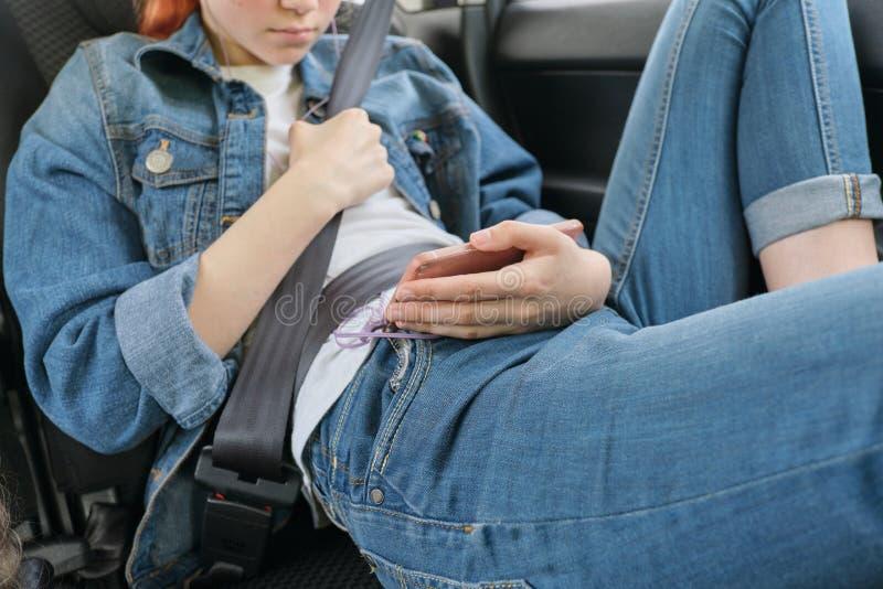 Ragazza teenager che si siede in automobile nel sedile del passeggero posteriore con lo smartphone e le cuffie immagini stock