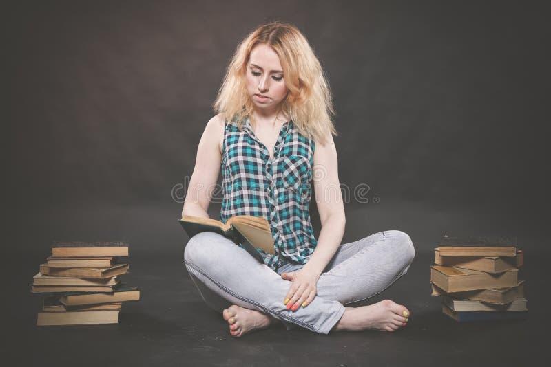 Ragazza teenager che si siede sul pavimento accanto ai libri e che mostra emozionalmente il suoi odio, odio ed affaticamento fotografie stock