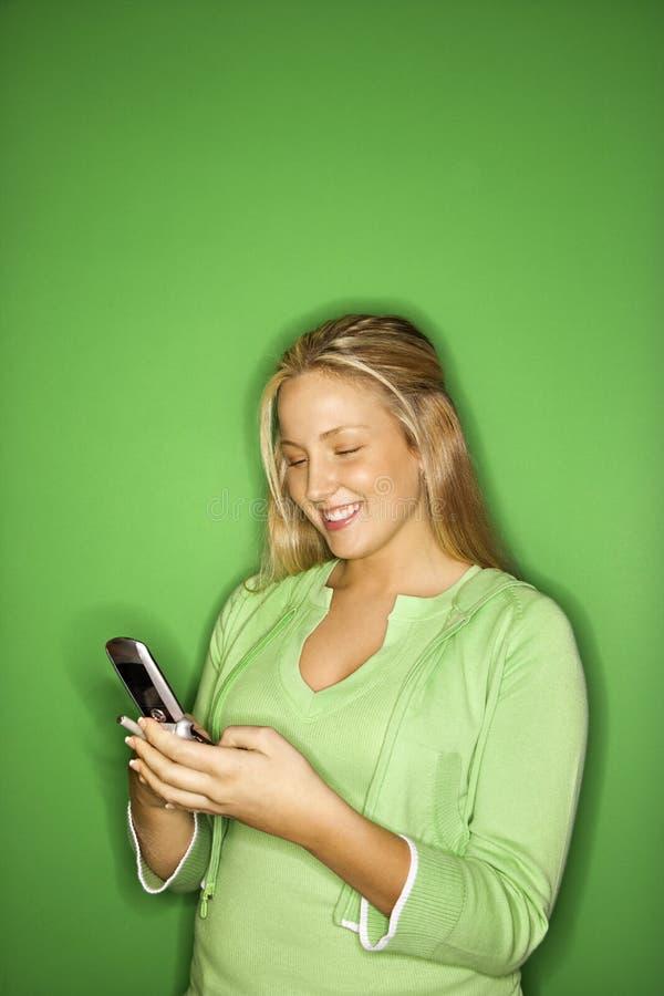 Ragazza teenager che sorride al cellulare fotografia stock