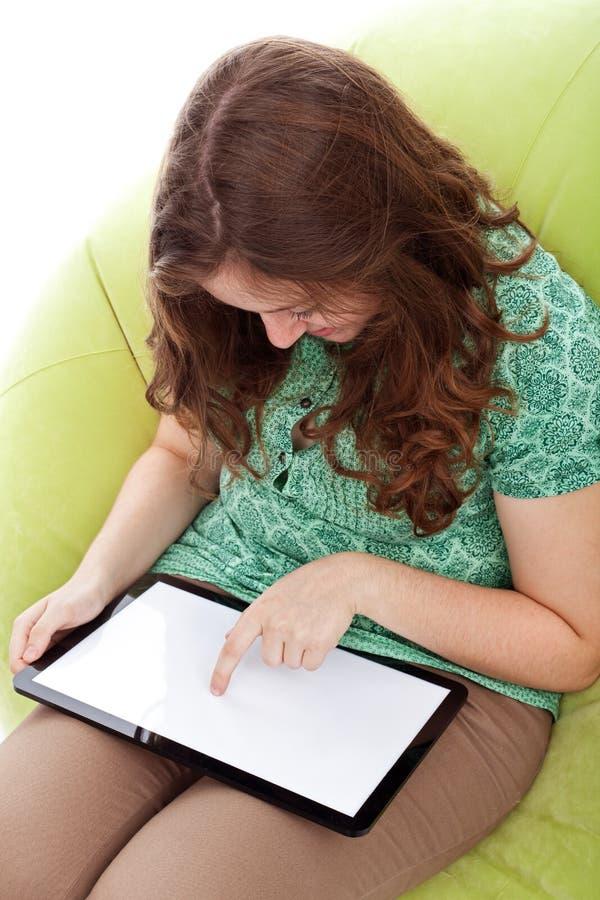 Ragazza teenager con il computer della compressa immagine stock