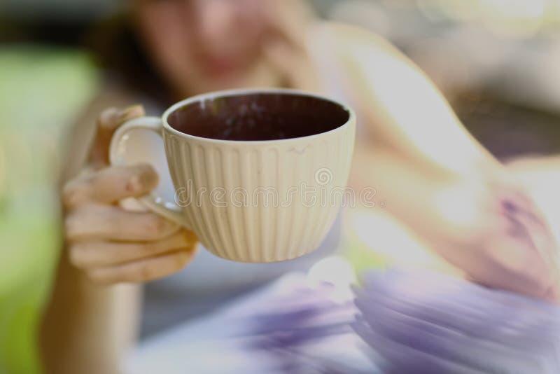 Ragazza teenager con la fine della tazza di tè della tenuta del libro sulla foto immagini stock
