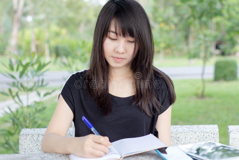 Download Ragazza Teenager Dello Studente Tailandese La Bella Scrive Un Libro Che Si Siede In Parco Fotografia Stock - Immagine di adulto, brunette: 55362488