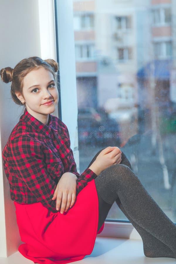 Ragazza teenager in gonna rossa che si siede sul davanzale della finestra immagine stock - Finestra che non si chiude ...