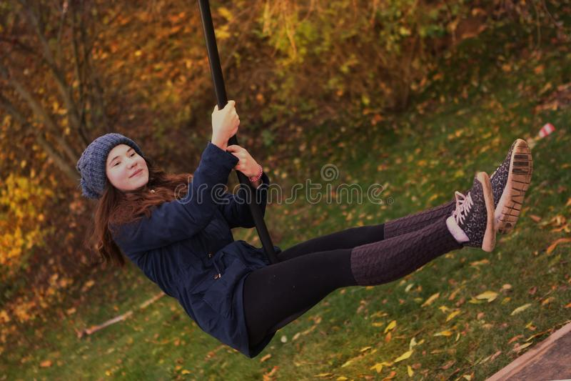 Ragazza teenager in mezzo tubo flessibile delle guaine di lana calde che oscilla nel parco della città di autunno fotografie stock