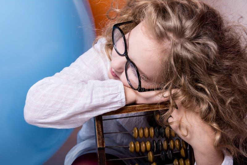 Ragazza teenager riccia divertente e abile in vetri con l'abaco di legno sulla t fotografia stock