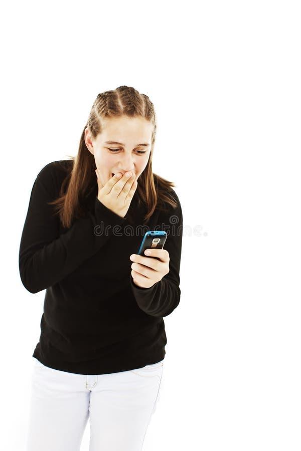 Ragazza teenager sorpresa che esamina il telefono mobile fotografia stock libera da diritti