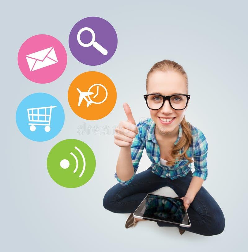 Ragazza teenager sorridente che si siede sul pavimento con il pc della compressa immagini stock