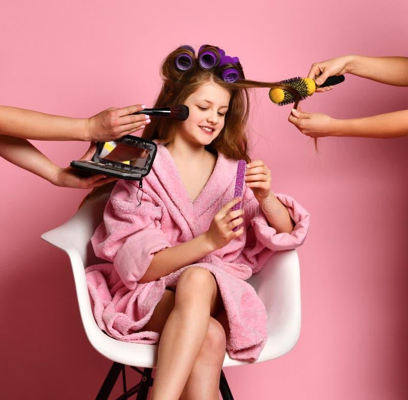 Ragazza teenager sorridente della giovane signora nel salone della stazione termale fare stile ed il manicure di capelli sul rosa fotografie stock libere da diritti