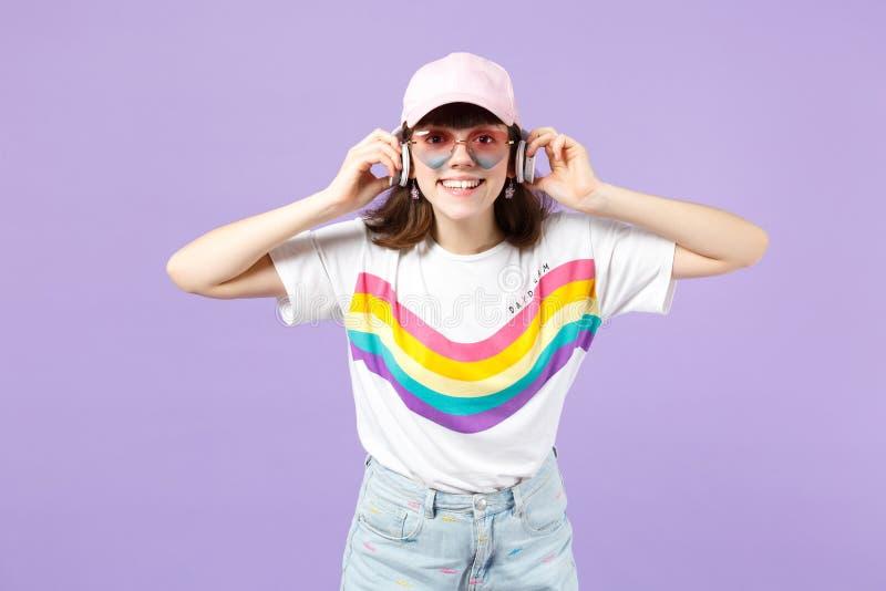 Ragazza teenager sorridente in vestiti vivi, musica d'ascolto degli occhiali del cuore con le cuffie isolate sulla parete pastell fotografie stock libere da diritti