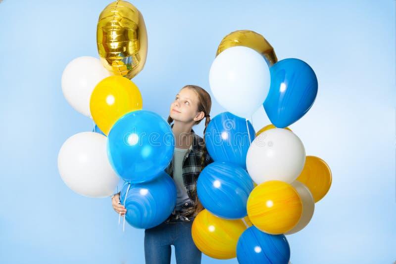 Ragazza teenager sveglia che tiene un mazzo di palloni variopinti immagini stock