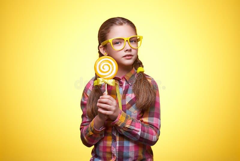 Ragazza teenager sveglia con la lecca-lecca su fondo giallo immagine stock libera da diritti
