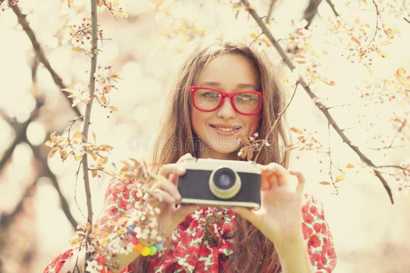 Ragazza teenager in vetri con la macchina fotografica d'annata vicino all'albero del fiore immagine stock libera da diritti