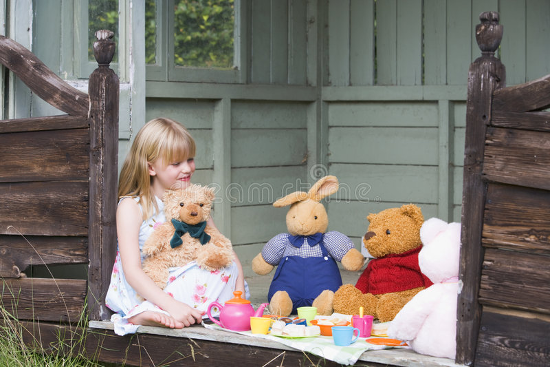 Ragazza in tettoia che gioca tè e sorridere immagine stock