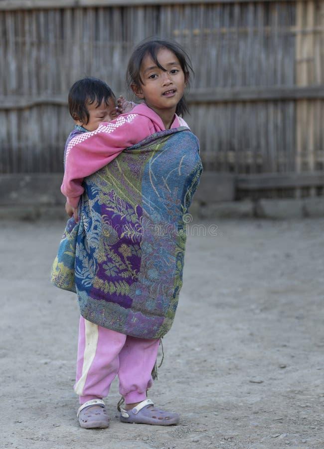 Ragazza tribale del giovane Naga che porta suo fratello germano su lei indietro al villaggio di Khonoma il 4 dicembre 2016 al vil immagini stock libere da diritti