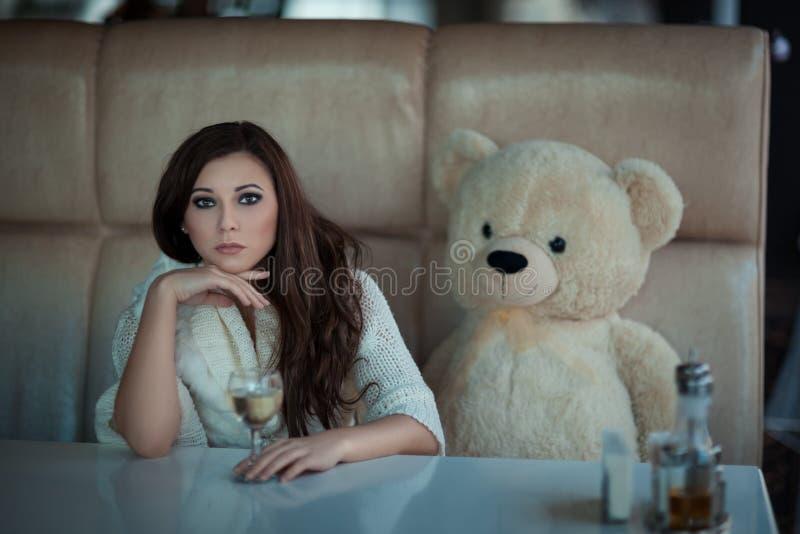 Ragazza triste alla tavola con un orso del giocattolo immagini stock