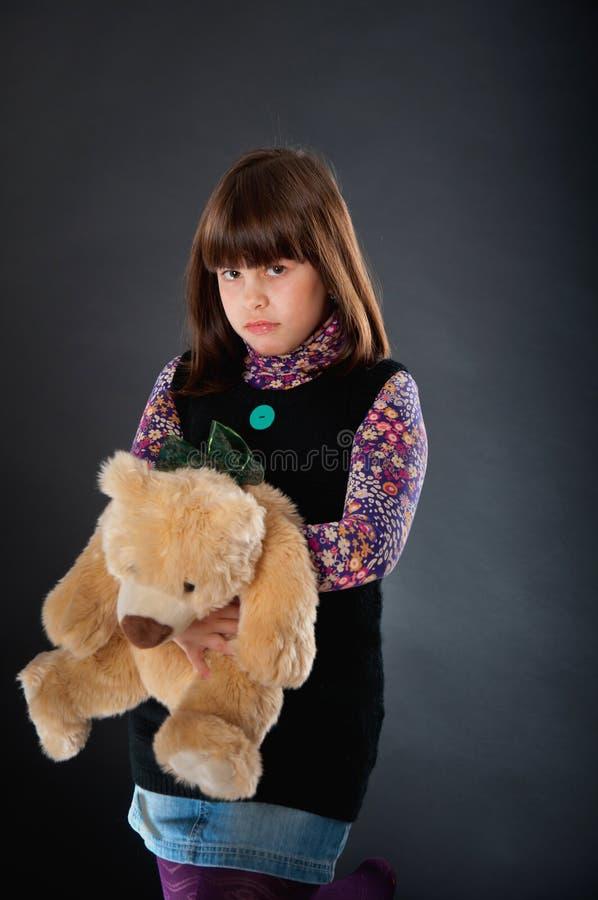 Ragazza triste che gioca con un orso di orsacchiotto