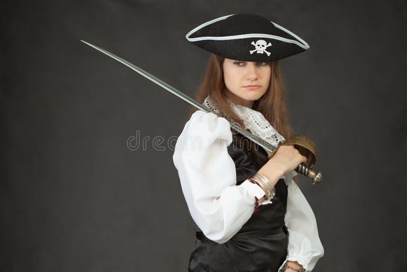 Ragazza triste in costume del pirata con il sabre fotografie stock