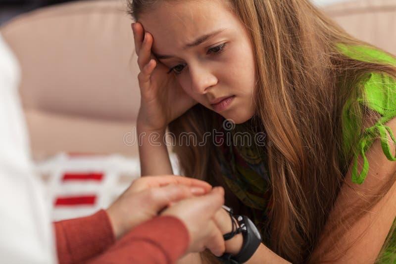 Ragazza triste dell'adolescente al consiglio - mani professionali tenuta della donna ed a confortare ragazza fotografie stock libere da diritti